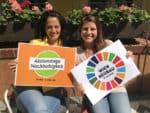 Das Bild zeigt zwei MitarbeiterInnen des Österreichischen Ökologie Instituts die Schilder halten. Ein Schild zeigt das Logo Aktionstage Nachhaltigkeit und eines das Logo der Globalen Nachhaltigkeitszielen