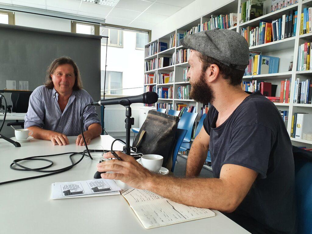 Ein Mann interviewt einen anderen Mann für ein Podcast-Gespräch.